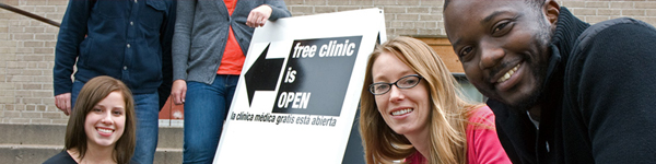 "A diverse group of smiling people standing next to a sign that reads ""Free clinic is open."""