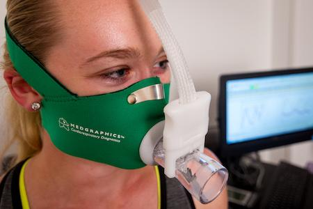 A woman wearing a V02 mask to measure her oxygen intake while running.